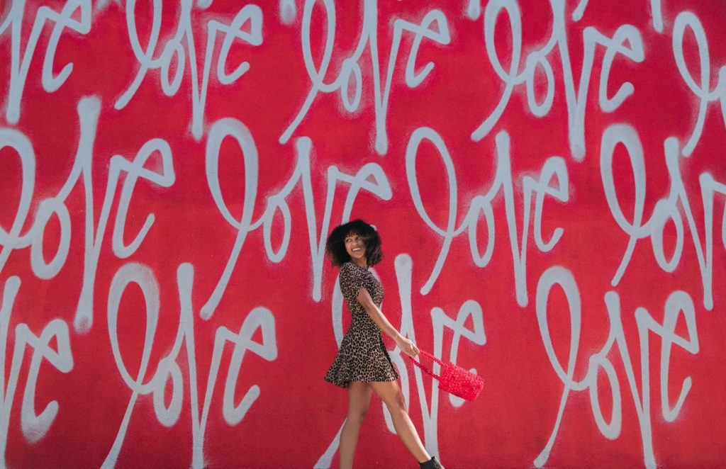 "girl in front of wall with ""love"" written several times all over it"