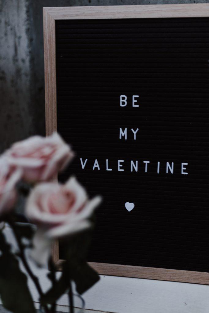 """be my valentine"" written on a board"