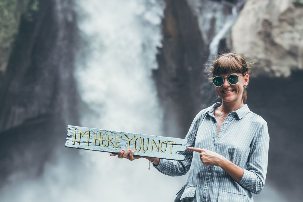 """girl in front of waterfall holding board meant to cause envy that reads """"I'm here, you not"""""""