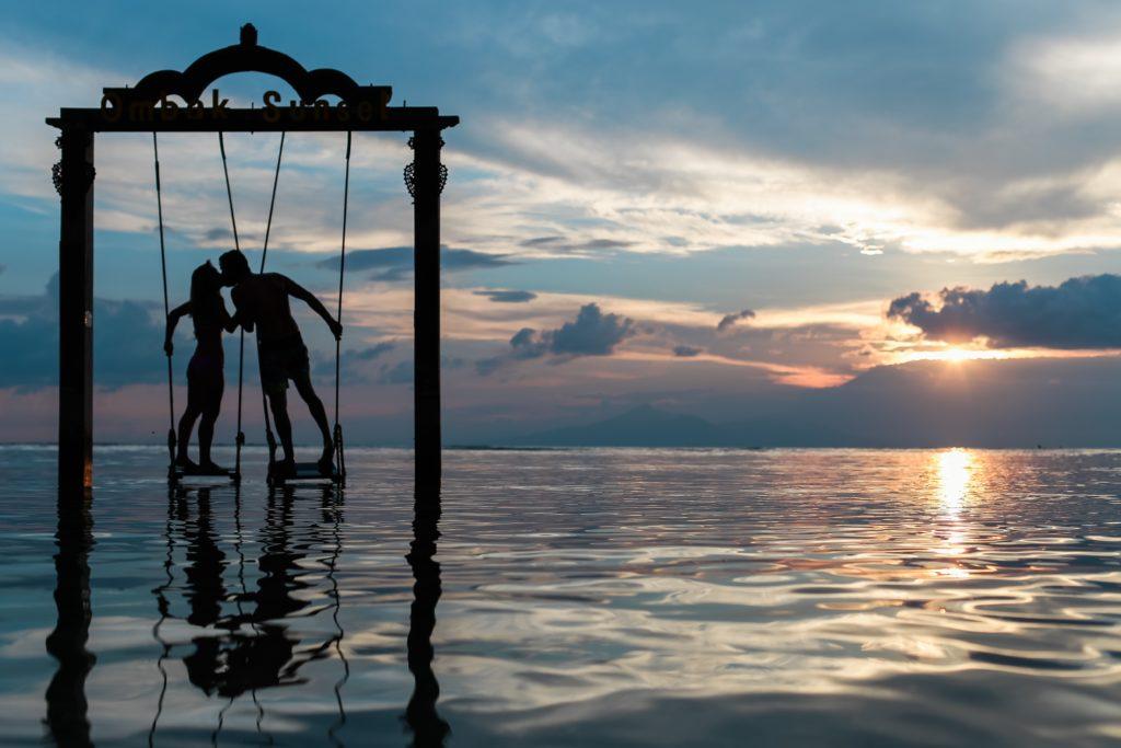 couple kissing on swing on lake at sunset