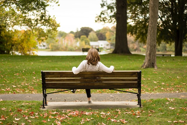 sufferer of philophobia sitting alone in a park