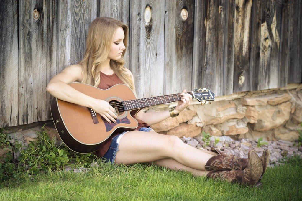 girl practicing the guitar in garden