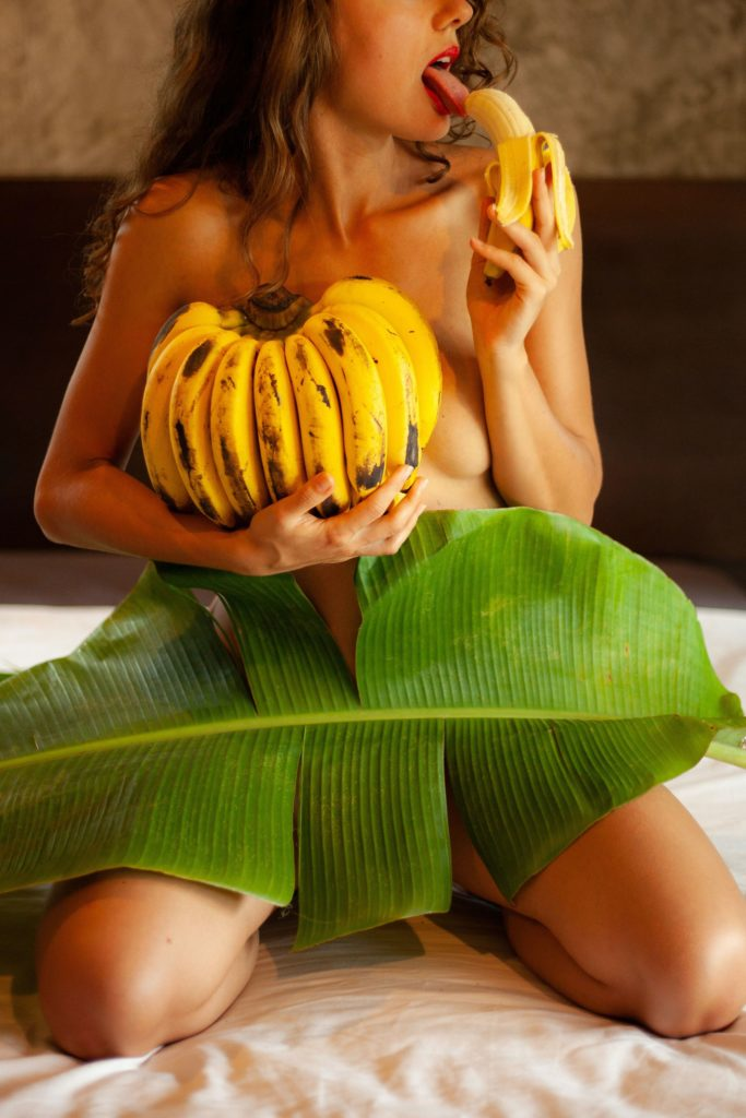 woman licking a banana while holding a bunch