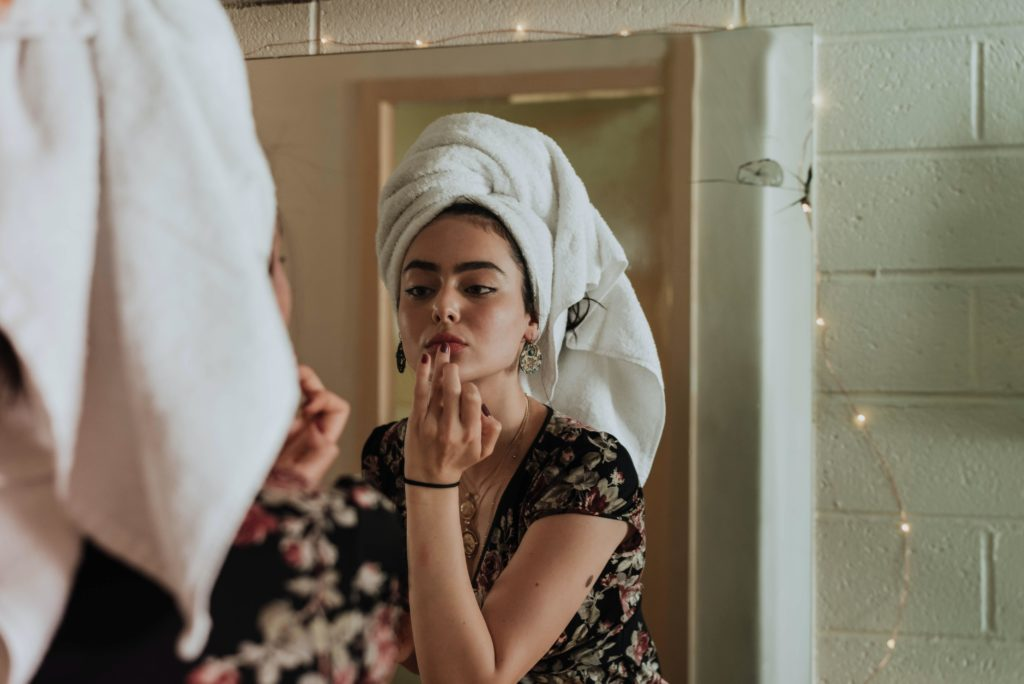 girl in front of mirror doing her beauty routine