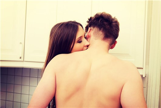 man and woman cheat together in kitchen