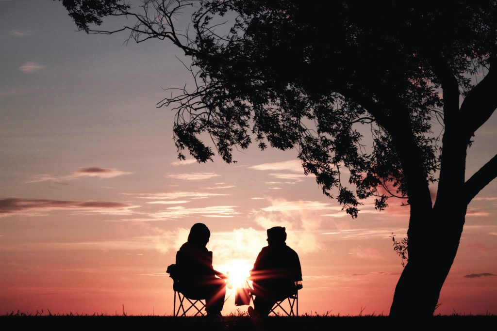 woman sitting with distant man under a tree