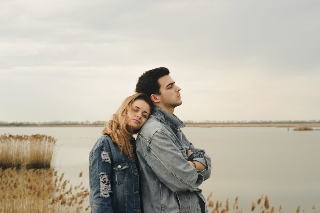 woman leaning her head on the shoulder of her distant boyfriend