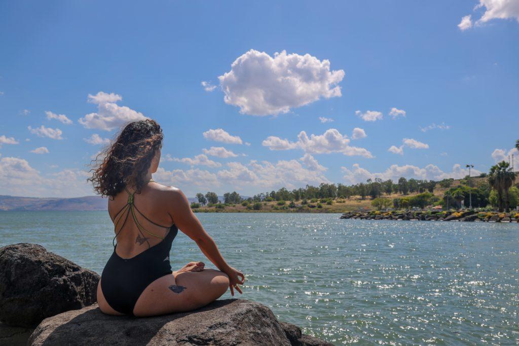 girl fasting and meditating at beach
