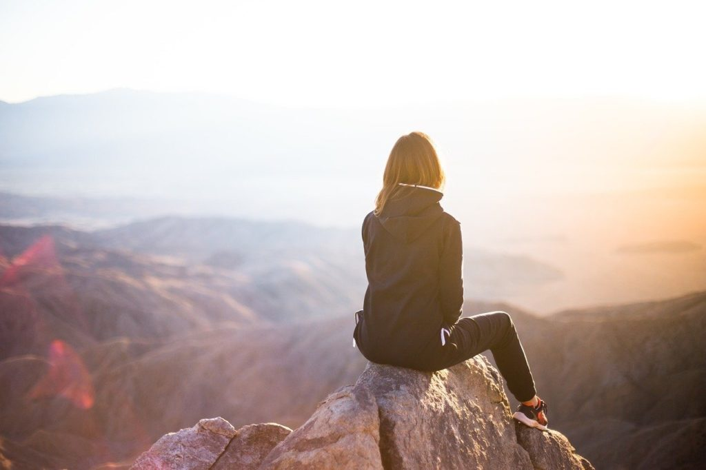 self-confident girl reflecting on top of mountain