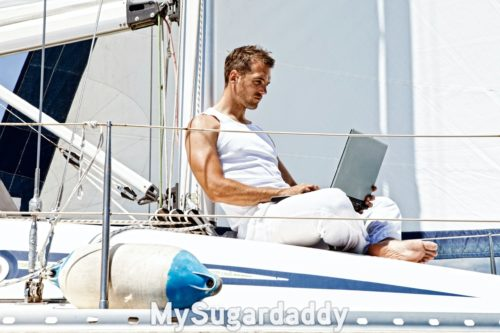 man using his laptop on a boat, example of a good picture for a sugar daddy profile