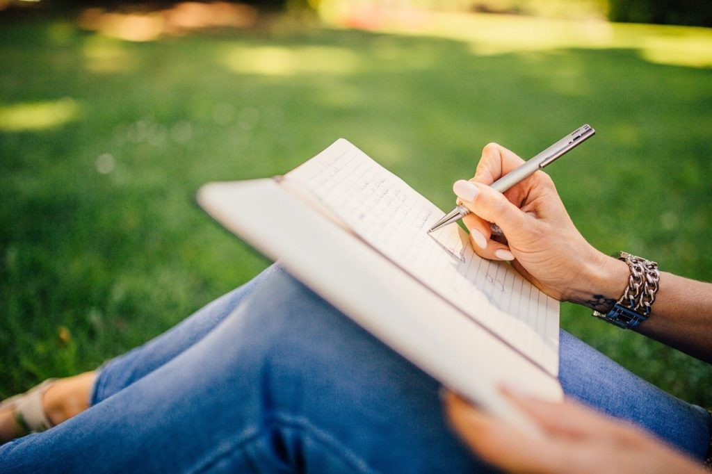 woman writing in her journal by hand on lawn