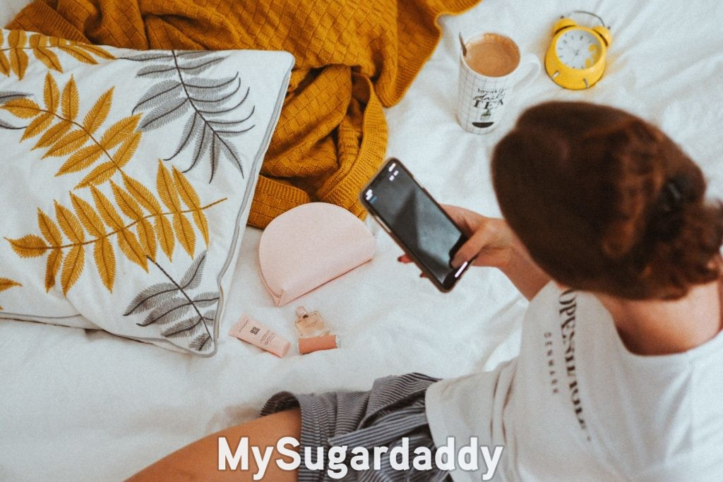 sugar baby distracting from her feelings in bed with her phone