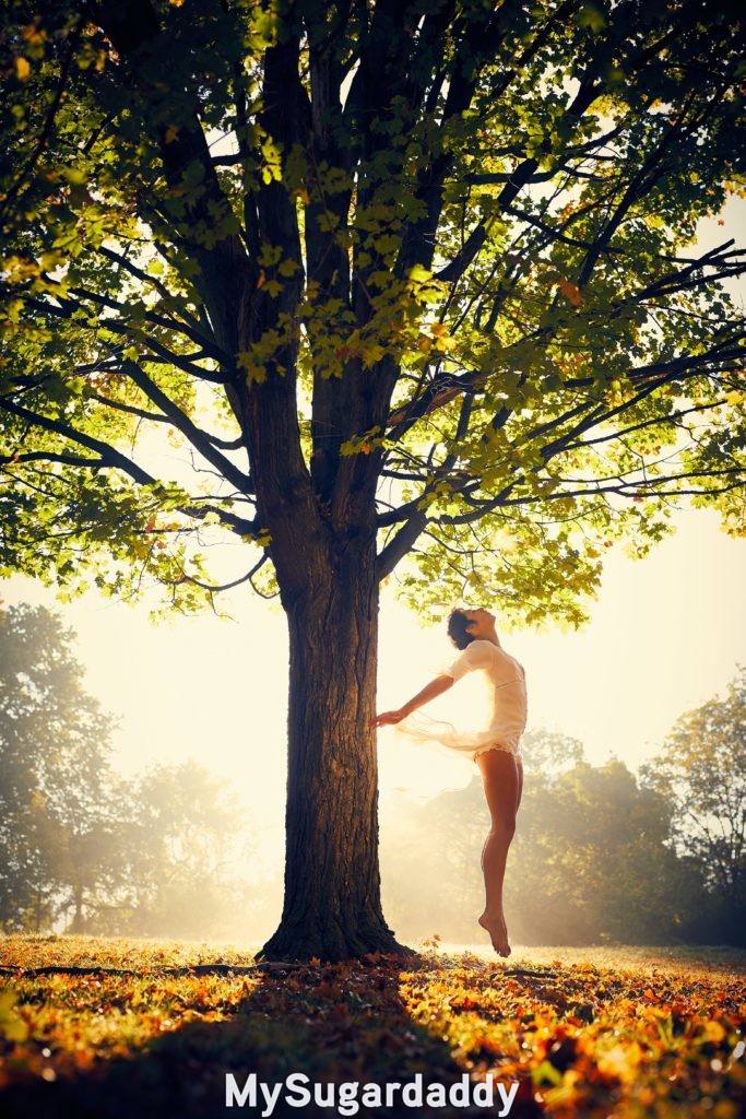 girl jumping near a tree