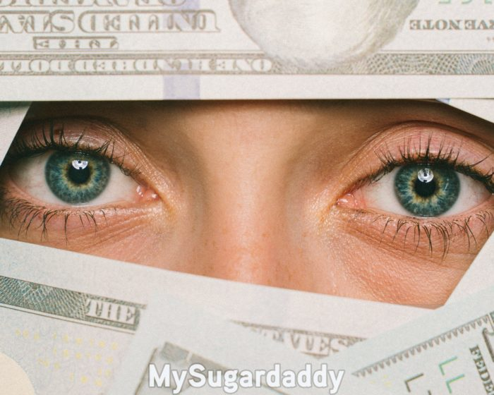 woman with her monthly allowance partially covering her face
